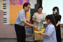 家長義工協助小一午膳2_學生有禮貌地從校長手中接過餐盒