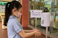 學生使用自動感應洗手機消毒-scaled