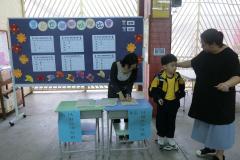 老師和家長義工協助量度書包的重量